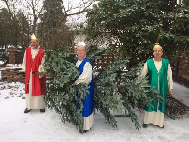 The three kings take away the Christmas tree into the snow.